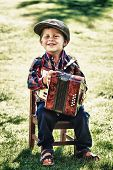 picture of newsboy  - Happy young boy playing accordion in summer - JPG