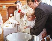 stock photo of christening  - Little baby boy being baptized in catholic church holding by father - JPG
