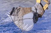 stock photo of dredge  - Excavator bucket dredging sand and gravel from the seafront - JPG