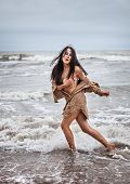 stock photo of seminude  - Beautiful young seminude woman in the cold sea waves - JPG