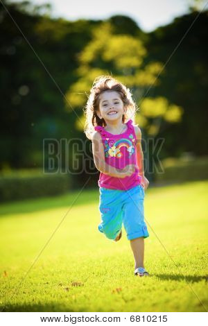 Young Excited And Smiling Girl Running In The Grass