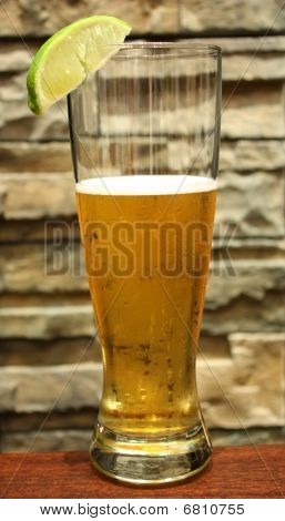 Refreshing beer with lime, brick background