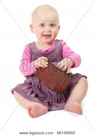 Happy smiling little girl in violet dress sits