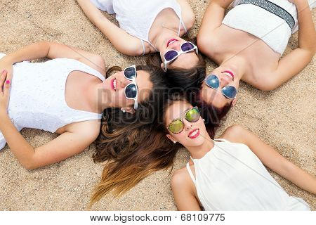 Cute Teen Girls Joining Heads Together On Sand.