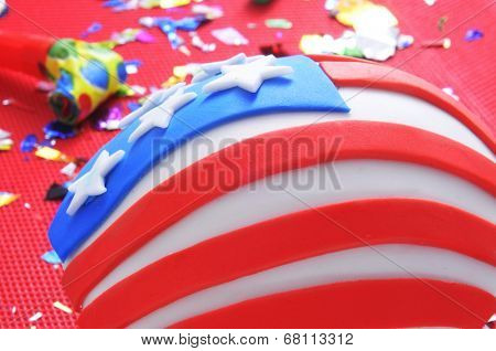 a cupcake decorated as the United States flag on a table with a red tablecloth with a party horn and confetti