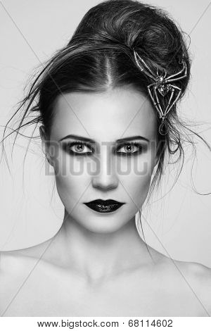 Black and white portrait of young beautiful woman with stylish gothic make-up and hairdo