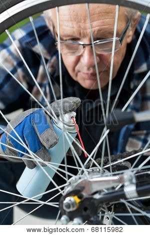 Man Cleaning And Oiling A Bicycle Chain