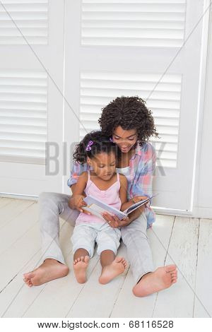 Mother and daughter sitting on the floor reading storybook at home in the living room
