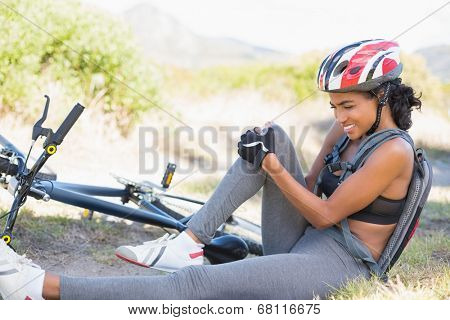 Fit woman holding her injured knee after bike crash on a sunny day in the countryside