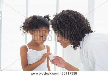 Pretty mother showing her daughter face cream at home in the bathroom