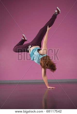 Pretty break dancer doing handstand with one hand in the dance studio