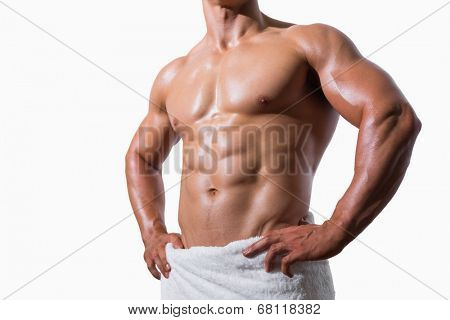 Mid section of a shirtless muscular man in white towel over white background