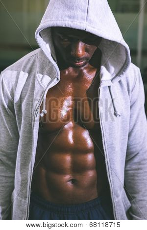 Muscular young man in hood jacket at the gym