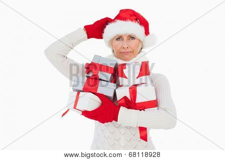 Festive woman scratching head and holding gifts on white background