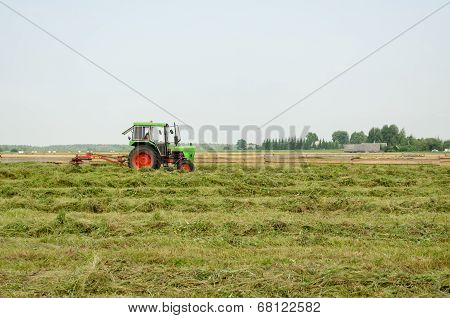 Tractor Turning Raking Cut Hay In Field