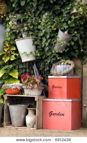 A Lovely Garden Wall Displaying Garden Equipment, Plantings, And Decorative Boxes