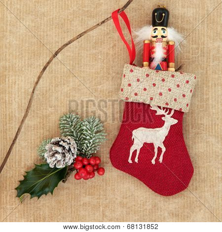 Christmas stocking and toy soldier drummer decoration, holly, snow covered fir and pine cone over brown paper background.