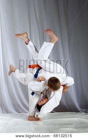 Sportsmen with a blue and orange belt are doing judo throws