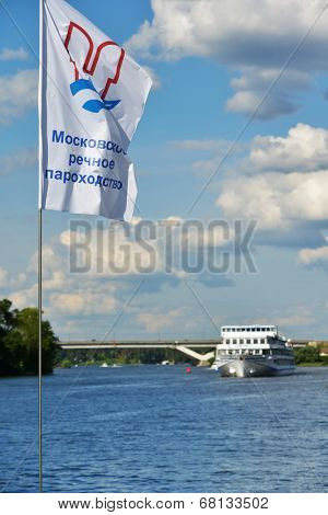 MOSCOW, RUSSIA - JULY 4, 2014: Flag of Moscow River Shipping Company against the ship on the Moscow canal. Founded in 1857, now the company manages 26 enterprises with more than 5700 employees