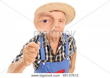 Mature farmer looking through a magnifying glass isolated on white background