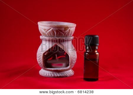 Aromatherapy Oil Burner With Bottle On Red Background