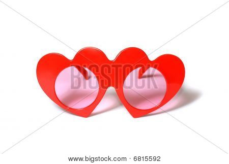 Red heart-shaped glasses on white