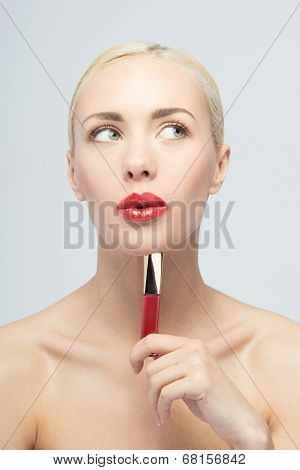 Beautiful woman applying lip gloss