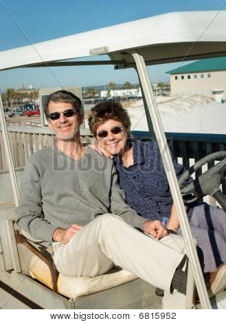 Retired Couple In Old Golf Cart At The Beach