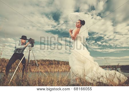 Groom using vintage photo camera outdoors  on the rock