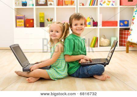 Happy Kids mit Laptops sitzen auf dem Boden