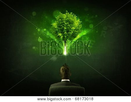 Young businessman sitting in office chair with a glowing tree and letters above his head