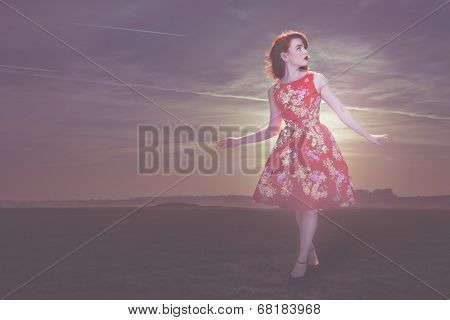 Beautiful graceful redhead woman in an red floral dress walking through ethereal misty landscape looking away to the right, with copyspace