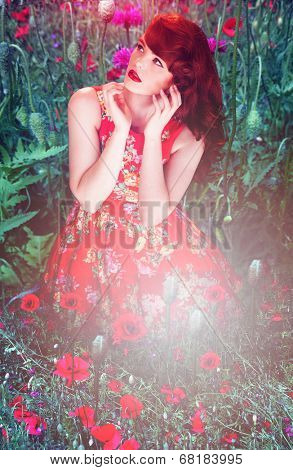 Artistic portrait of a beautiful redhead woman sitting in a red floral dress amongst red poppies looking up with a dreamy expression, bright flare effect in the foreground