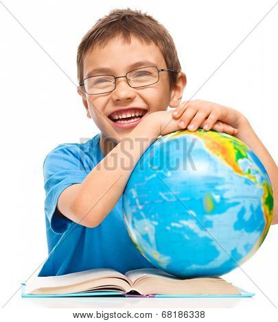 Little boy is examining globe while sitting at table, isolated over white
