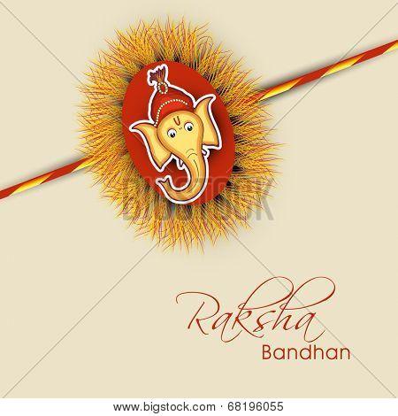 Beautiful rakhi decorated with Hindu mythology Lord Ganesha face on brown background for Happy Raksha Bandhan.