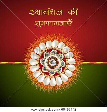 Beautiful rakhi on red and green background for Happy Raksha Bandhan celebrations.