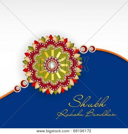 Beautiful rakhi on grey and blue background for the occasion of Happy Raksha Bandhan celebrations.