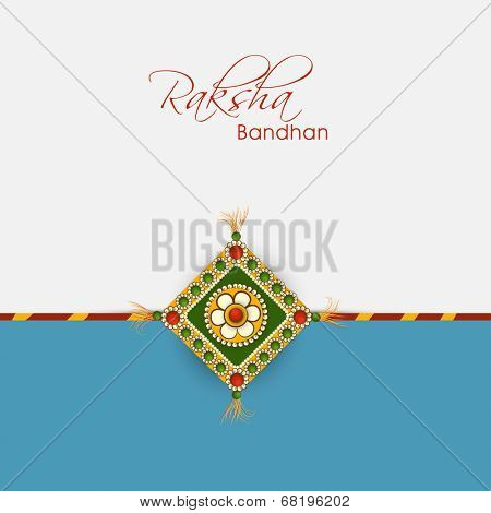 Beautiful greeting card design with elegant rakhi on grey and blue background for Happy Raksha Bandhan celebrations.