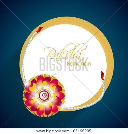 Beautiful rakhi with golden circle frame on blue background for Happy Raksha Bandhan celebrations.