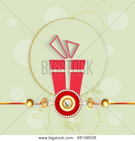 Beautiful greeting card design with rakhi and red gift box on green background for Happy Raksha Bandhan celebrations.