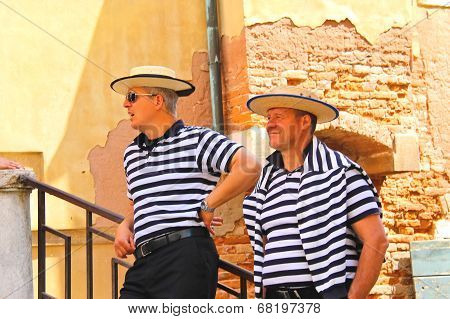 Two Gondoliers On The Docks Awaiting Tourists In Venice, Italy