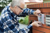 foto of handyman  - Handyman in flannel shirt fixing intercom horizontal - JPG