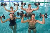 stock photo of day care center  - Happy fitness class doing aqua aerobics with foam dumbbells in swimming pool at the leisure centre - JPG