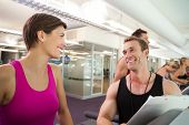 stock photo of treadmill  - Trainer talking to his client on the treadmill at the gym - JPG