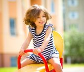 foto of playground  - Young happy girl is swinging in playground - JPG