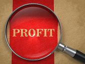 foto of profit  - Profit through Magnifying Glass on Old Paper with Red Vertical Line - JPG