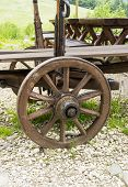 image of chassis  - Decorative wagon wheel with wooden chassis in a rustic ambient