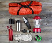 stock photo of tent  - Overhead view of basic hiking gear placed on weathered wooden boards - JPG