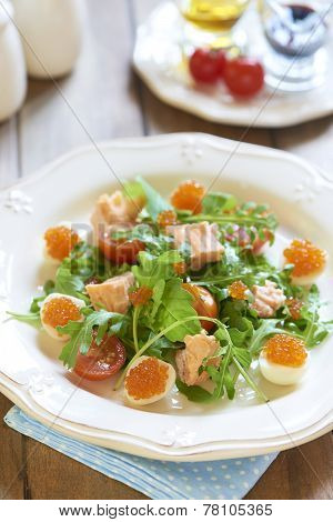 Fresh salad with salmon, quail eggs, cherry tomatoes and red caviar