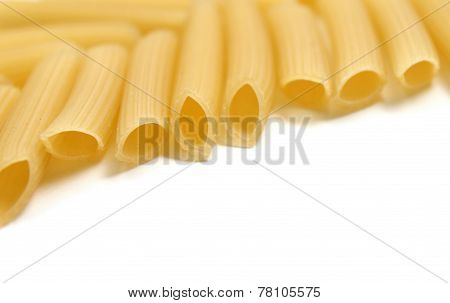 Some raw penne macaroni on white background